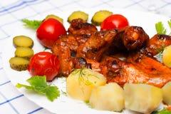 Huhn grillte mit gekochten Kartoffeln und legte Tomaten in Essig ein Lizenzfreie Stockbilder