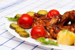 Huhn grillte mit gekochten Kartoffeln und legte Tomaten in Essig ein Lizenzfreies Stockbild
