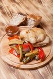 Huhn mit Gemüse diente auf rundem Schneidebrett auf gebrannt Lizenzfreies Stockfoto
