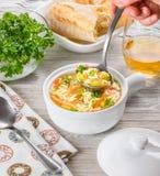 Huhn-orzo Suppe in einem weißen Topf auf hölzernem Hintergrund Italienische Suppe mit orzo Teigwaren Chef ` s Hand, die einen Sch lizenzfreies stockfoto