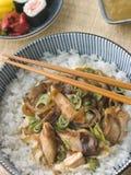 Huhn und Ei auf Reis mit Essiggurken und Sushi Stockbild