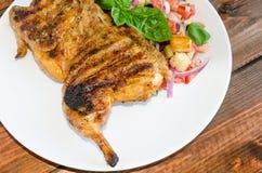 Huhn unter einem Ziegelstein mit panzanella Salat Lizenzfreie Stockbilder