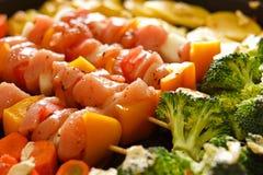Huhnaufsteckspindeln mit Gemüse in der schwarzen Wanne Stockfoto