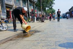 Pouring slops. The Hui nationality man is pouring slops in street of Pingyao, Shanxi, China Stock Photo