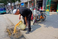 Pouring slops. The Hui nationality man is pouring slops in street of Pingyao, Shanxi, China Stock Photos