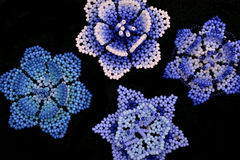 Huichol blue flowers. Colorful mexican craftwork  created by huichol people in Jalisco, Mexico.Tiny beads are handwoven to create their sacred flower Stock Photo