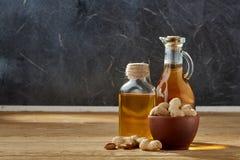 Huile aromatique dans un pot et une bouteille en verre avec des arachides dans la cuvette sur la table en bois, plan rapproché images libres de droits