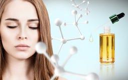 Huile cosmétique d'amorce près de visage de femme avec la grande chaîne de molécule Image stock