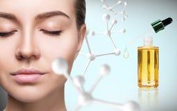 Huile cosmétique d'amorce près de visage de femme avec la grande chaîne de molécule Images stock