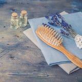 Huile cuir chevelu et de brosse et de peigne et de cheveux en bois de massage avec la lavande naturelle sur le fond rustique Photos stock
