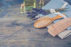Huile cuir chevelu et de brosse et de peigne et de cheveux en bois de massage avec la lavande naturelle sur le fond rustique Photo stock