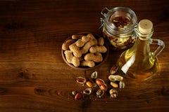 Huile d'arachide dans la bouteille et des écrous secs sur la table en bois Vue supérieure photographie stock