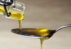 Huile d'olive au-dessus de cuillère Photographie stock libre de droits
