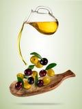 Huile d'olive avec des olives de vol dans la cuvette en bois Photo libre de droits