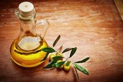 Huile d'olive avec les olives fraîches sur le bois rustique Photographie stock