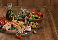 Huile d'olive avec les olives vertes et le pain sur une surface en bois Image stock
