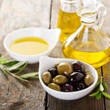 Huile d'olive dans des bouteilles et une cuvette avec des olives Photographie stock libre de droits