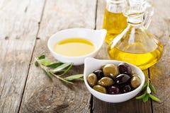 Huile d'olive dans des bouteilles et une cuvette avec des olives Photo libre de droits