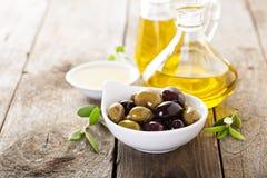 Huile d'olive dans des bouteilles et une cuvette avec des olives Photos libres de droits