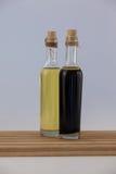 Huile d'olive dans des bouteilles sur la table en bois Image stock