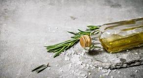 Huile d'olive dans la bouteille avec le romarin et le sel Images libres de droits