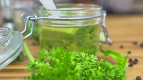 Huile d'olive dans le pot en verre avec des herbes pour faire cuire sur la table en bois Huile d'olive de Vierge pour la cuisine  banque de vidéos