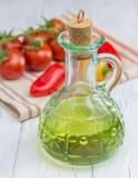 Huile d'olive dans le pot en verre avec les tomates et le paprika photographie stock