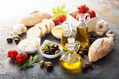 Huile d'olive en bouteilles de vintage et ingrédients italiens de cuisine Photographie stock libre de droits