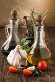 Huile d'olive et vinaigre, gralic, tomates avec des herbes Image stock