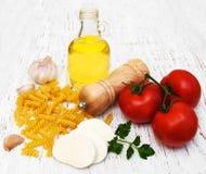 Huile d'olive, fromage de mozzarella, pâtes de fusilli, ail et tomates Image libre de droits