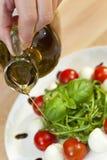 Huile d'olive préparant la salade de Rocket de mozzarella de tomate Image stock