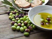 Huile d'olive sur la table en bois avec du pain Photographie stock