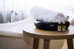 Huile de bain blanche de serviette et de massage sur la table dans la salle de bains Images stock