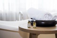 Huile de bain blanche de serviette et de massage sur la table dans la salle de bains Photographie stock