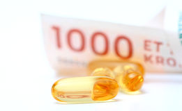 Huile de foie de morue Omega 3 capsules de gel avec le billet de banque de devise de 1000 couronnes danoises Photos stock