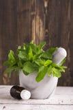 Huile de menthe poivrée et feuilles en bon état fraîches au-dessus de table en bois Photos libres de droits