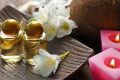 Huile de noix de coco en bouteilles et fleurs sur le plateau en bois, Photographie stock libre de droits