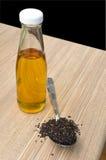 Huile de sésame et les graines de sésame noires dans la cuillère sur la table en bois Photos stock