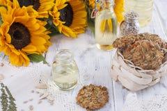 Huile de tournesol et grandes fleurs jaunes Pétrole dans la bouteille Sans peau des graines et des biscuits de tournesol Fond en  images libres de droits