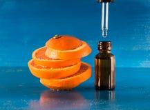 Huile essentielle avec les tranches, la bouteille et le compte-gouttes oranges Photo stock