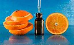 Huile essentielle avec les tranches, la bouteille et le compte-gouttes oranges Photos stock