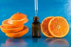 Huile essentielle avec les tranches, la bouteille et le compte-gouttes oranges Image stock