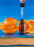 Huile essentielle avec les tranches, la bouteille et le compte-gouttes oranges Images libres de droits