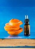 Huile essentielle avec les tranches, la bouteille et le compte-gouttes oranges Photo libre de droits