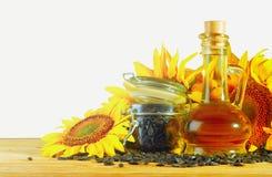 Huile, graines et tournesols de tournesol sur la table Image libre de droits