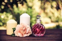 Huile rose parfumée dans une belle bouteille en verre Élixir, bougies et fleurs roses Concept de station thermale Teinture de vin Photo libre de droits