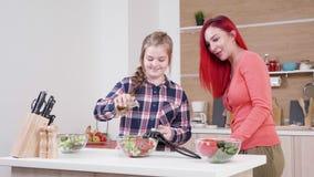 Huile se renversante de fille sur la salade tandis que sa mère est près de elle banque de vidéos
