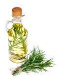 Huilez dans une bouteille et un romarin organique frais d'isolement sur le blanc Image libre de droits