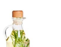 Huilez dans une bouteille et un romarin organique frais d'isolement sur le blanc Photographie stock libre de droits