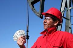 Huilez l'ouvrier avec les factures modifiées de dollar US de fixation de visage Image stock